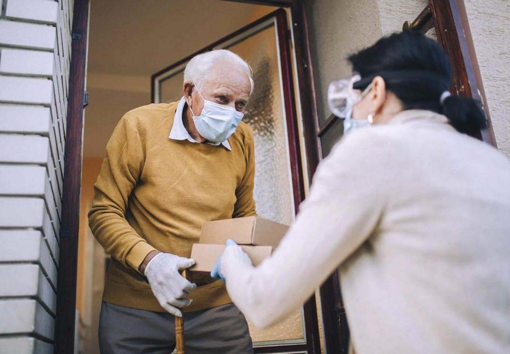 Older gentleman receiving supplies from woman at front door