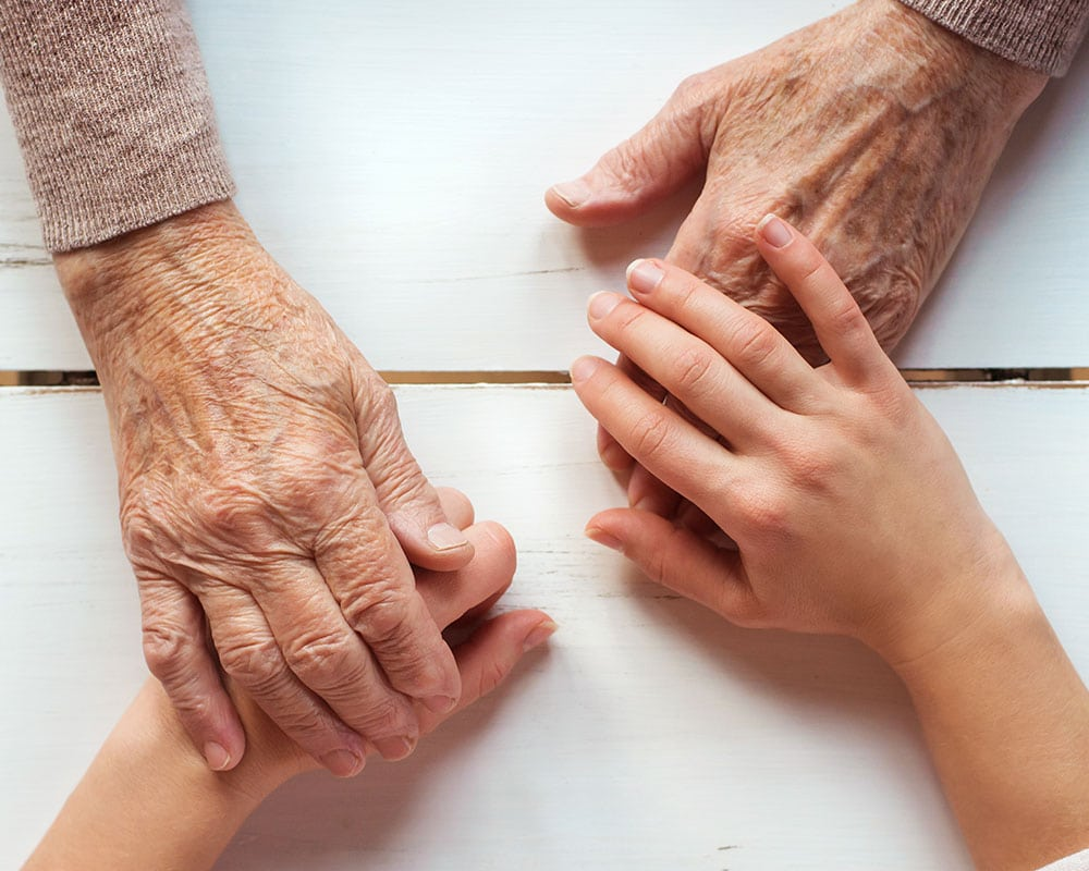 Elderly hands and child's hands touching